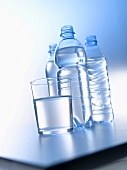 Glass of water and three bottles of water on a table