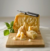 Parmesan with knife and basil on a wooden board