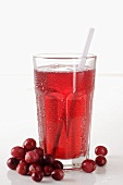 A glass of cranberry juice with a straw