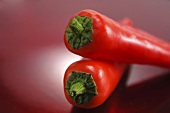 Two red pointed peppers, one lying on top of the other