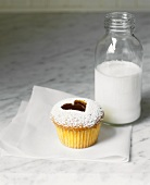 A cupcake with a jam heart and a bottle of milk