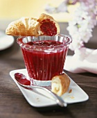 Redcurrant and vanilla jam in a jar with croissant