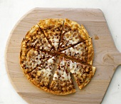 A mince pizza, divided into portions, on a wooden board