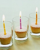 Three cupcakes with burning candles in glasses