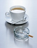 A cup of coffee with a cigarette in an ashtray