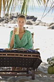 Woman sitting at table on beach with food & pineapple juice