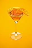 An orange cocktail with orange zest