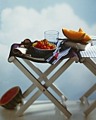Summer cuisine: melon, tomatoes on stools, book, sunglasses