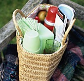 Basket of picnic things on a wooden bench