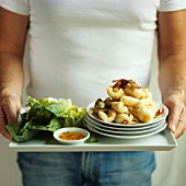 Man holding deep-fried squid and chilli dip on tray