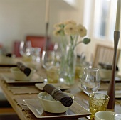 Laid table with fabric napkins, candles and flowers