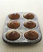 Six chocolate muffins in a muffin tin