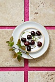 Fresh cherries with a small cherry branch on a plate