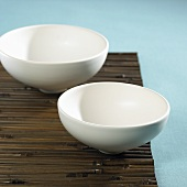 Two porcelain bowls on a bamboo mat