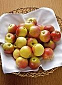 Apples on a white napkin in a wicker basket