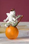 Porcelain angel with cinnamon, star anise & sage on orange