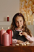 Girl sitting at table with candles and Christmas biscuits
