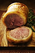 Roast saddle of lamb, partly carved, with rosemary on board
