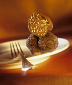 Black truffles on plate with fork