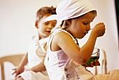 Little girl eating jelly, little boy watching