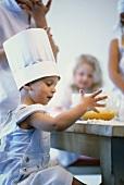 Little boy baking, siblings watching