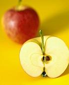 Ein ganzer Apfel und eine Apfelhälfte auf gelbem Untergrund