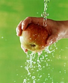 A Hand Holding an Apple Under a Stream of Water