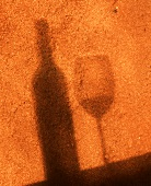Shadow of a Wine Bottle and Glass on Sand Stone Wall
