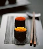 Gunkan maki with two sorts of caviare on black platter