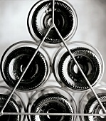The bottoms of Bordeaux bottles in wine rack (b and w negative)