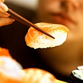 A Piece of Sushi Being Held on Chopsticks