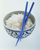 Cooked rice in Asian bowl with chopsticks