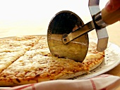 A Pizza Cutter Slicing Through a Cheese Pizza