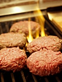 Several Hamburger Patties on the Grill with Flames