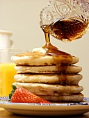 Pouring Syrup Over a Stack of Pancakes
