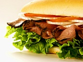A Roast Beef Sub with Tomatoes, Onions and Lettuce