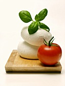 Two Mozzarella Balls with Basil and Tomato on Wooden Board