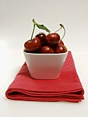 Dish of Red Cherries Resting on a Red Napkin