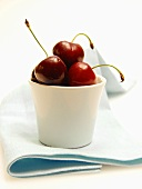 Several Cherries in a White Cup Resting on a Blue Cloth