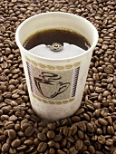 Black Coffee in a Paper Cup Resting On Coffee Beans