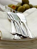 Butter Knifes Resting on Linen Napkins with Olives
