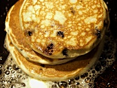 Three Blueberry Pancakes Cooking on a Grill with Butter