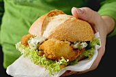 Hand holding fish burger with remoulade sauce
