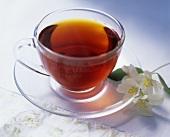 A cup of black tea, jasmine flowers beside it
