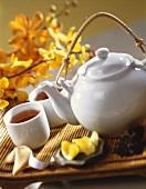 Teekanne und Teebecher auf einer Bambusmatte