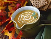 Cream of pumpkin soup with cobweb pattern & autumn leaves