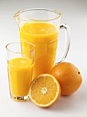 Orange juice in jug and glass, fresh oranges