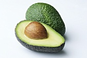 Half an avocado with stone and a whole avocado