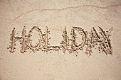 The word HOLIDAY written in sand