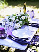 Place settings and flowers on a garden table